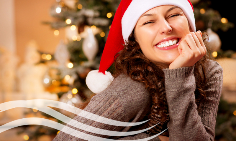 smiling woman in front of a tree wearing a holiday hat
